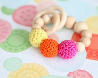 Teething toy with crochet wooden beads and 2 wooden rings. Yellow, pink, orange alternately small and big wooden beads rattle.