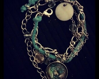 The Patterns Charm Bracelet with silver link chain on Teal Suede