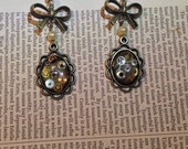 Steampunk earrings - bronze frames resin set with vintage watch parts hanging from a bow and pearl