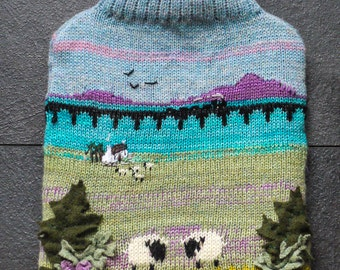 Knitted hot water bottle cover with viaduct, lake and grazing sheep design - bottle included