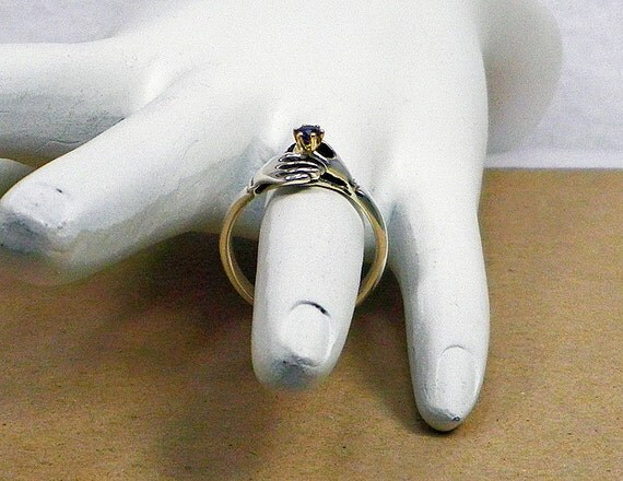 Two Hands Holding a Blue Sapphire Gemstone Claddaugh Ring in Sterling Silver and 14K Gold