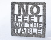 Coasters laser cut with 'No feet on the Table' in light grey felt