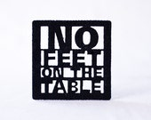Black felt coasters cut with 'no-feet-on-the-table' design