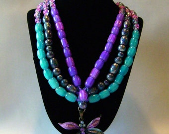 15.5 inch three tiered glass and acrylic bead necklace with a metal dragonfly pendant