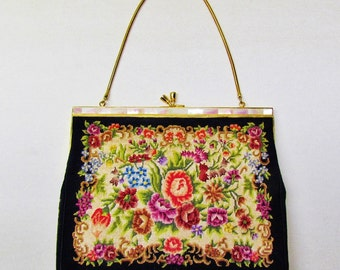 Vintage petit point purse with floral pattern on black background and mother of pearl frame