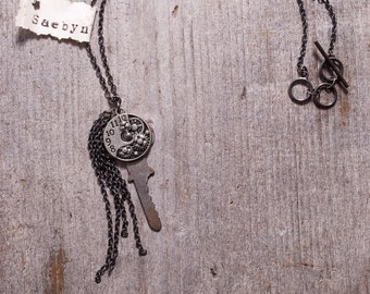 metal antique key necklace decorated  with clockwork gears and embelished with thin dark chain