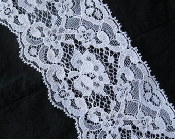 pretty vintage white lace with floral and scroll motifs, two scalloped edges, 2 1/2 inches wide
