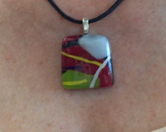 Fused glass pendant, black, dark red, olive green, white, and yellow