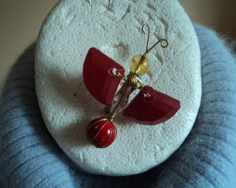 A gold wire and red beaded butterfly brooch
