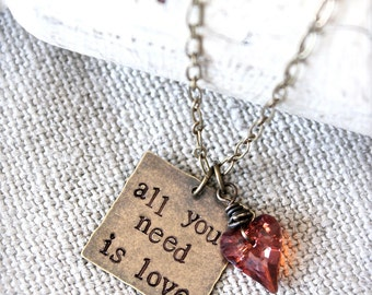 All you need is love.  Valentine's Day Quote inspirational charm necklace.  Hand stamped brass with Swarovski Wild Heart.  Valentine's Day