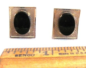 Cufflinks of brushed gold tone with black glass stone
