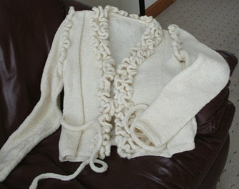 Close-fitting open front cardigan with ruffled edges and trims.
