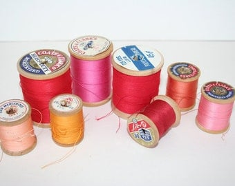 Lot of eight wooden spools of thread. Red, pink, peach, yellow, mercerized cotton, polyester.