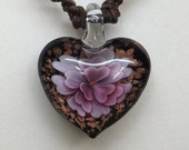 Lampwork glass puffed heart pendant macrame necklace with copper colored foil flakes set behing a beautiful lavendar floating flower