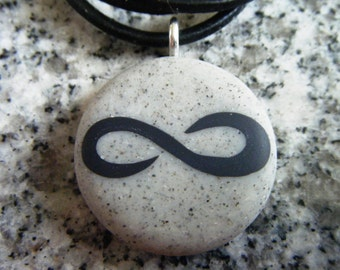 Infinity symbol hand carved on a polymer clay sand granite color background. Pendant comes with a FREE 3mm necklace.