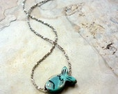 Plated silver delicate necklace with green patina fish pendant .