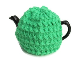 Knitted bright green tea cosy for a small pot.