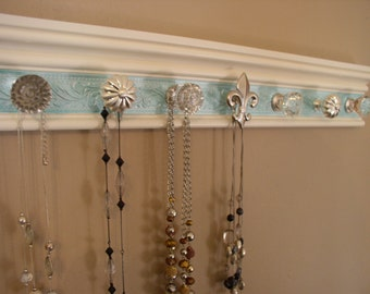 "Wall jewelry Rack. This necklace organizer has 7 knobs on off white with teal embossed background  20"" beautiful decor and storage"