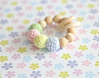 Rattle toy for baby, small teething ring in pastel colors. Wooden teether in light green, pink, blue and yellow.