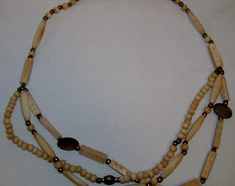 Multi strand necklace with carved bone and brass beads