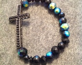 Black cross bracelet. Blue and black iridescent beads. Fits most wrists.