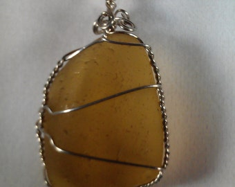 Pendant of amber colored seaglass, wrapped in silver finished wire