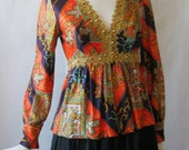 1960's golden gem encrusted print silky blouse, in rich glossy orange, purple, and multi paisley print, with gimp trim, long sleeve, small