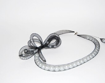 Bow black plastic mesh tube necklace with pearls inside. Pearls move within the tube.