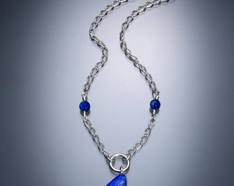 Handmade necklace with uniquely cut lapis pendant  on a sterling silver chain with small lapis accent beads and a lobster clasp