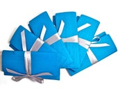 Silk bridesmaid clutches in turquoise with silver satin ribbon. Custom colors available.