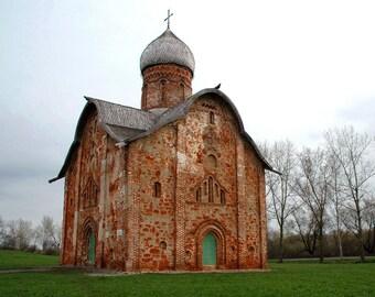 Ancient architecture. Landscape photography. Summer. Brick church. Wooden onion dome. Novgorod, Russia.