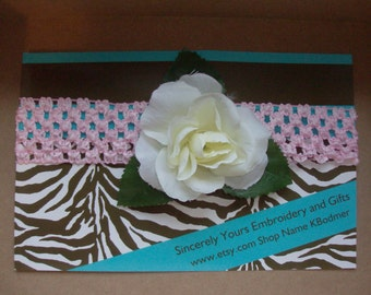 Adorable crochet headband accented with a sweet white rose
