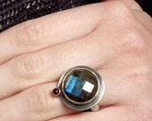 Handmade silver cocktail ring with blue rose cut labradorite and orbiting blood red rose cut garnet.