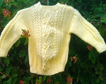 Child's boy girl toddler handknit yellow aran cable sweater with shoulder opening.