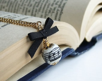 Music score bead and black ribbon bow necklace, gold plated chain
