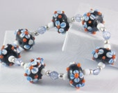 Beaded, Stretch Bracelet in Black with Blue and Orange Flowers