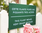 Funny sign for Flower gardens. Rose bush, Cactus Signage. French Humor. This Plant Wears Prickles