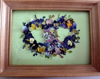 Pressed heart collage with violas and bleeding hearts in a frame