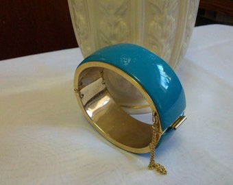 Beautiful gold tone clasp bracelet wrapped in blue plastic