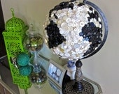 Globe covered in black and white vintage buttons with decorative base