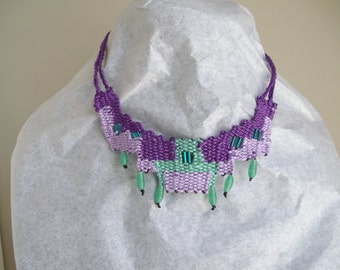 Woven necklace in purple and green with beads