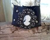 Black leather cameo cuff, distressed edges,embellishments, snap closure