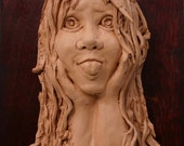 Young girl sticking out her tongue-  On wood background terracotta (fired clay) relief  -Home Decor