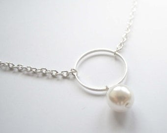 Elegant white pearl necklace with silver circle