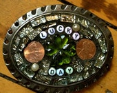 """belt buckle created with found objects and a very rare green,glass,shamrock. it's your """"lucky day!"""" now all you need  is a belt.peace."""