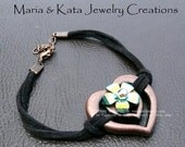 Leather cord w/ extension chain- has resin iridescent flower w/ silver bead