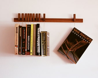 Custom made wooden book rack / bookshelf in Walnut. Pins also work as bookmarks. Bookcase