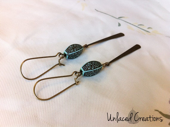 moira. a pair of simple brass drop earrings with etched turquoise beads.