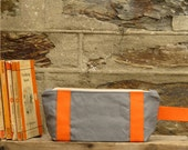Bright and bold Zip pouch/ toiletry bag. Ticking stripe lining. Industrial grey washed thick canvas. Orange accents, and a YKK brass zip.