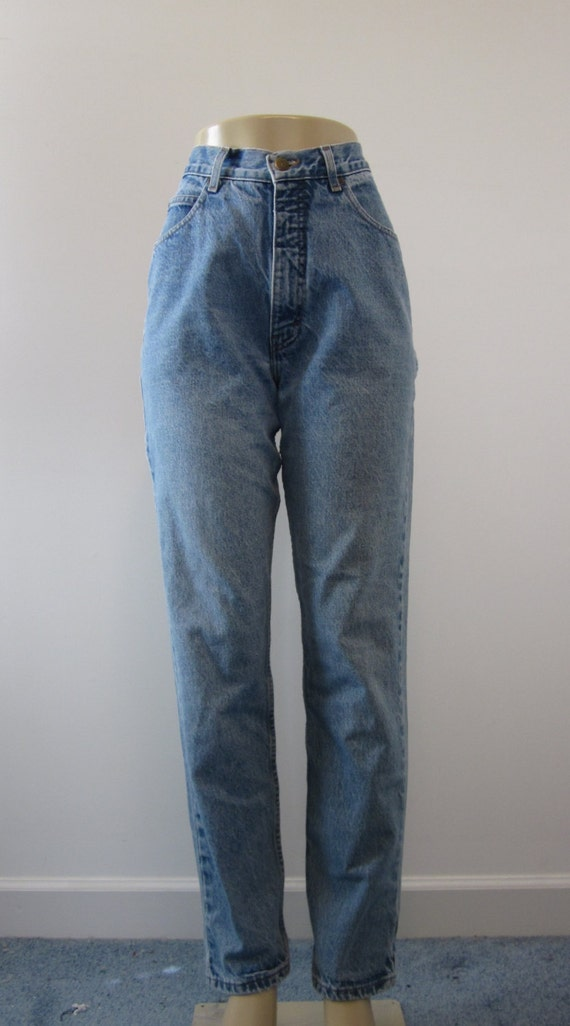 These jeans have a high rise, which includes a 2″ waistband. Belt loops appear around the circumference of the waistband. The jeans zip in front, and close with a .